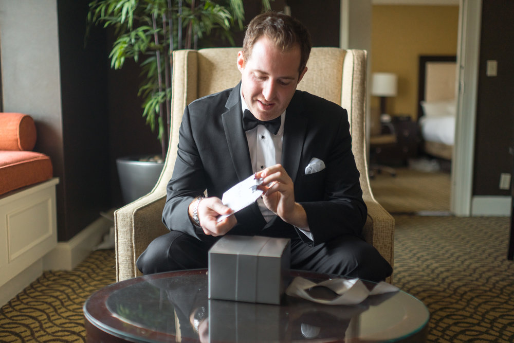Groom at Hyatt Regency Reston receives gift from bride photos by jessica nazarova