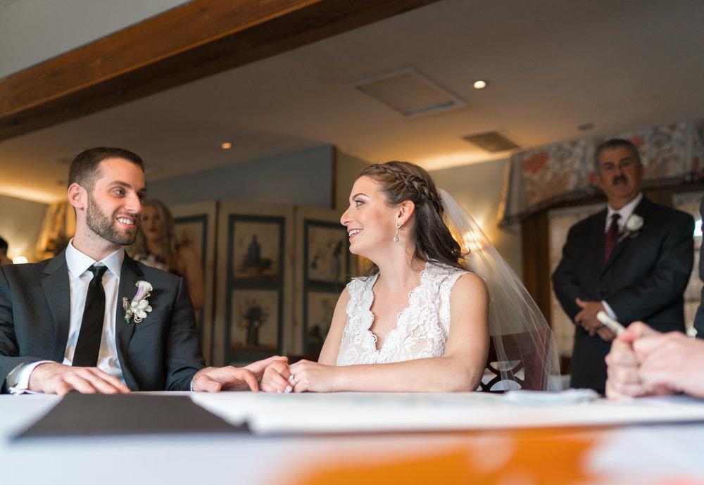 Bride and groom signing Ketubah at La Ferme wedding