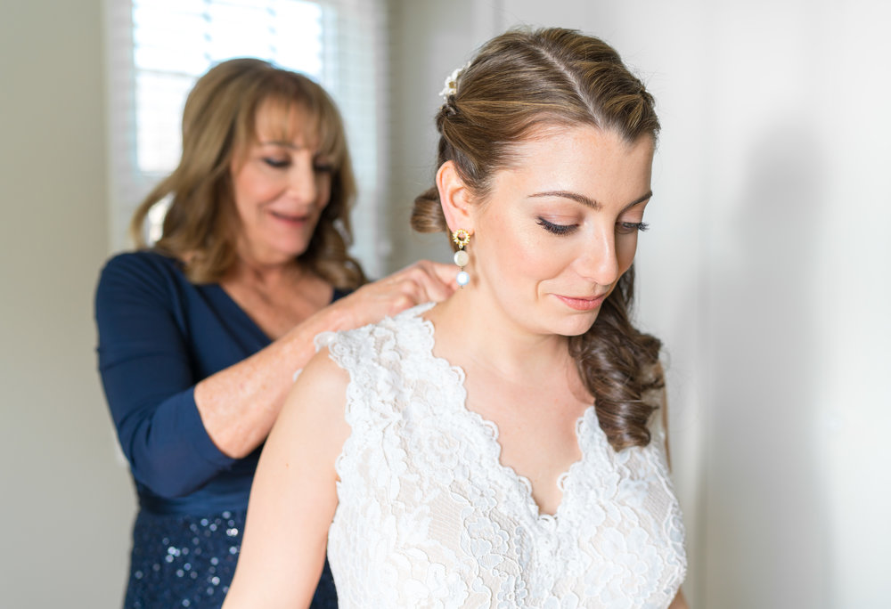 Mom buttoning bride's dress in Chevy Chase home
