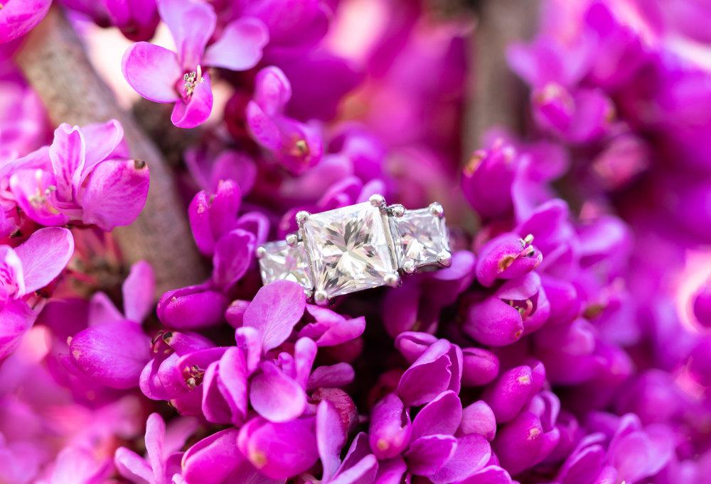 Three stone princess cut engagement ring on purple lilac