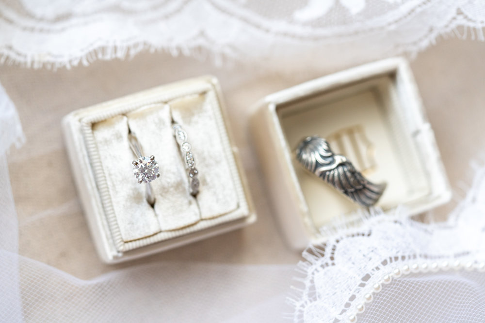Bride and groom's wedding rings at Harvest House in a Mrs. Box