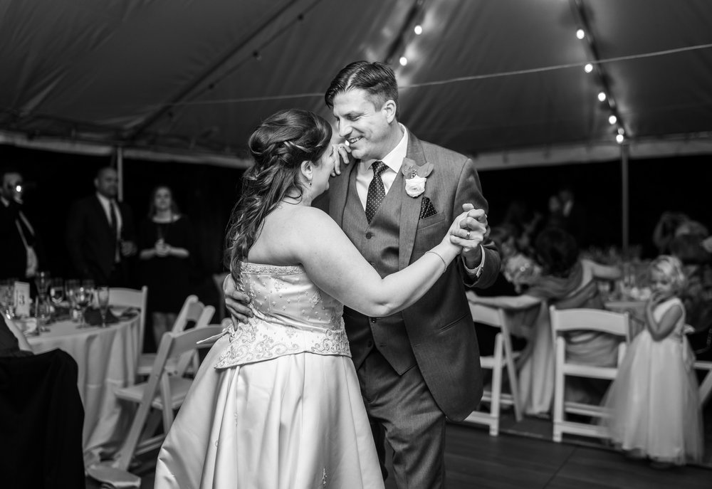 Black and white photo of bride and groom sharing their first dance under a tent at Hendry House