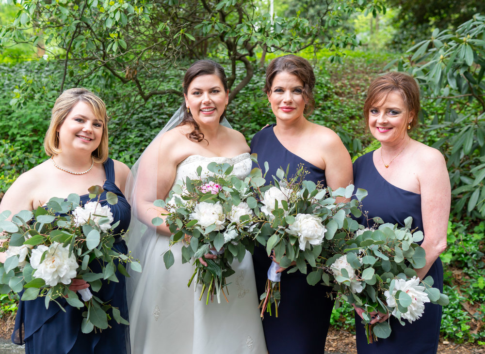 Bride and three bridesmaids in navy dresses and green bouquets at Hendry House