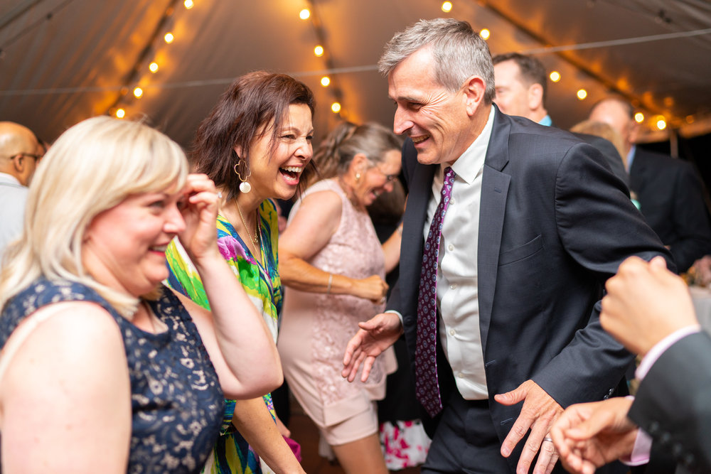 Guests laughing and dancing at Hendry House tented wedding reception with twinkle lights