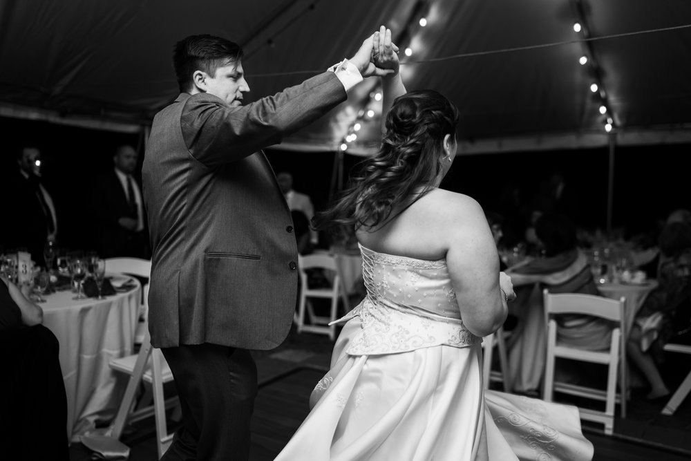 Black and white photo of a groom twirling his bride during the first dance at Hendry House wedding