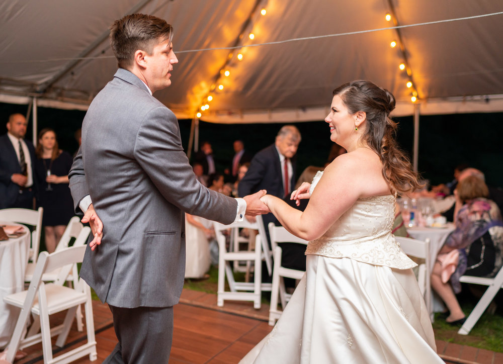 Bride and groom sharing their first dance with twinkle lights under a tent reception at Hendry House