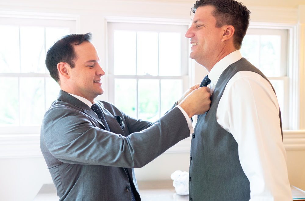 Groomsmen tying bow tie at Hendry House wedding