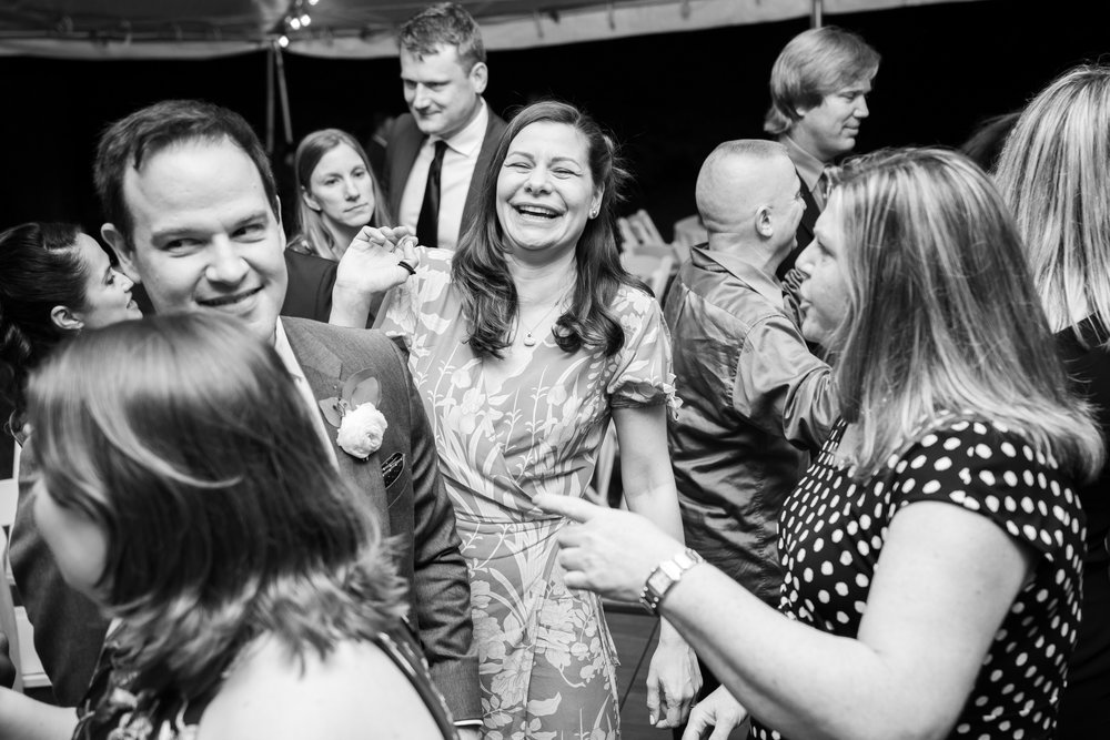 Black and white photo of wedding guests laughing on the dance at Hendry House