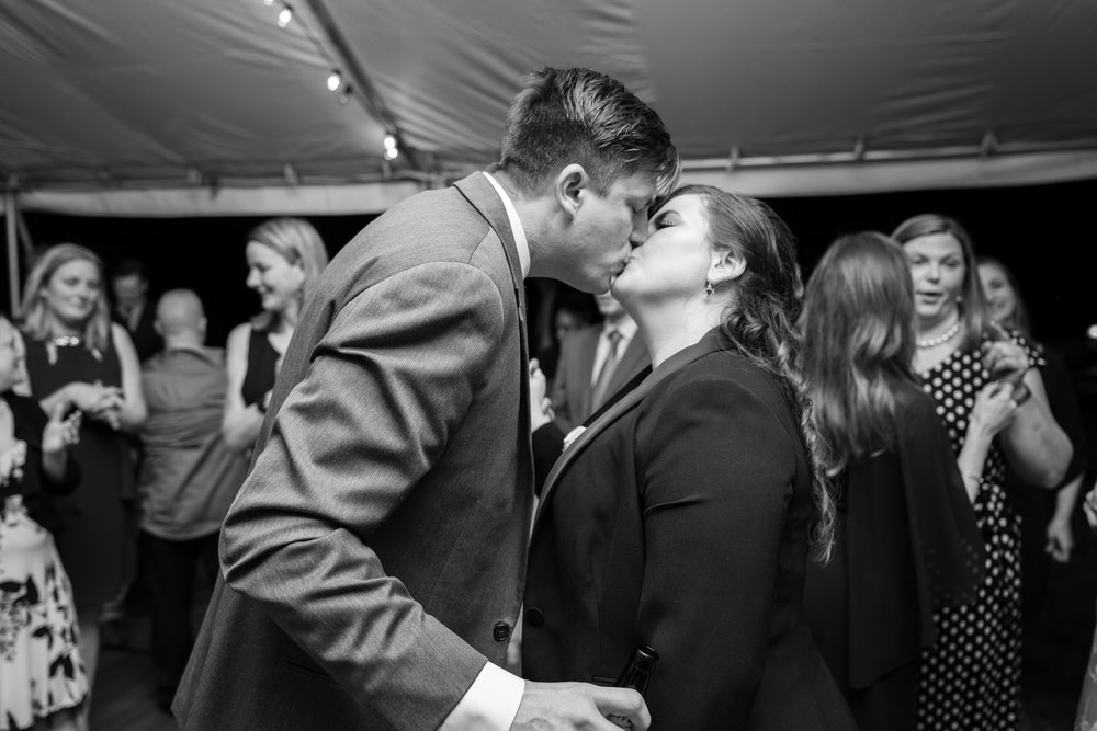 Black and white photo of bride and groom sharing their last kiss of the night at Hendry House wedding