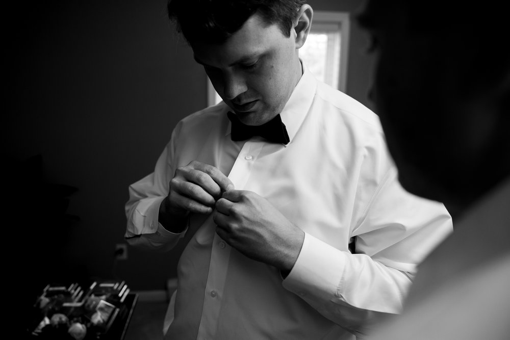 Black and white image of groom getting ready at Harvest House Lost Creek Winery