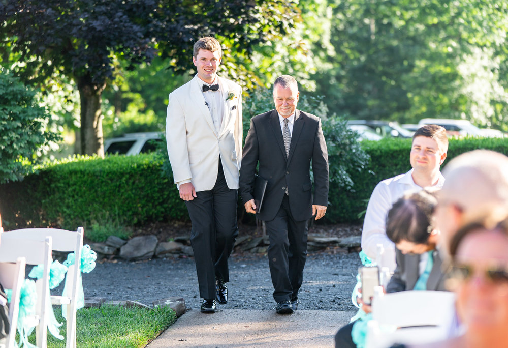 Groom walking down the aisle in front of Harvest House at Lost Creek Winery wedding