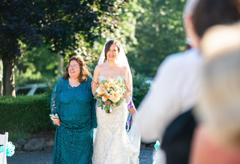 Bride walking down the aisle in front of Harvest House at Lost Creek Winery wedding