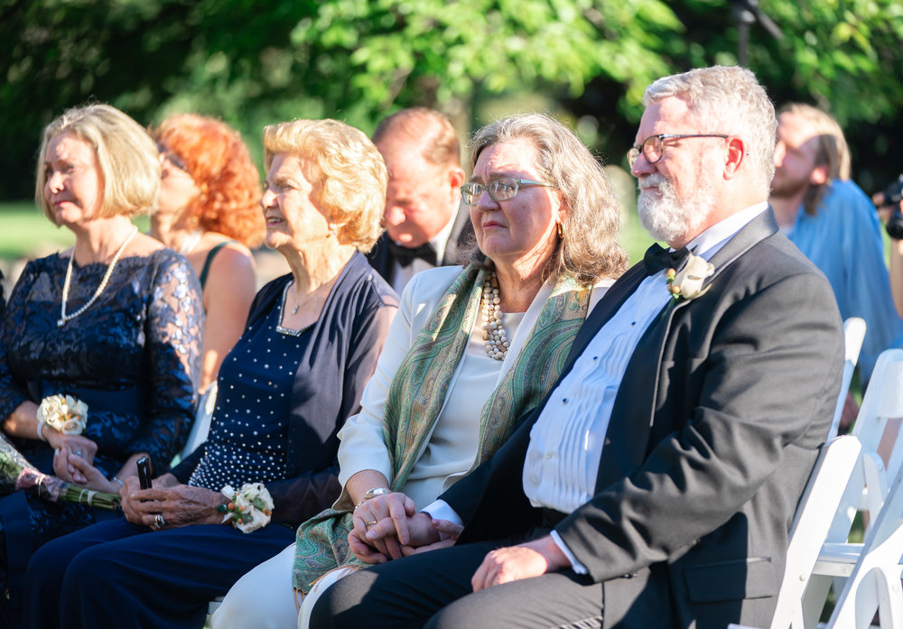 Groom's parents watching wedding ceremony at Harvest House at Lost Creek Winery