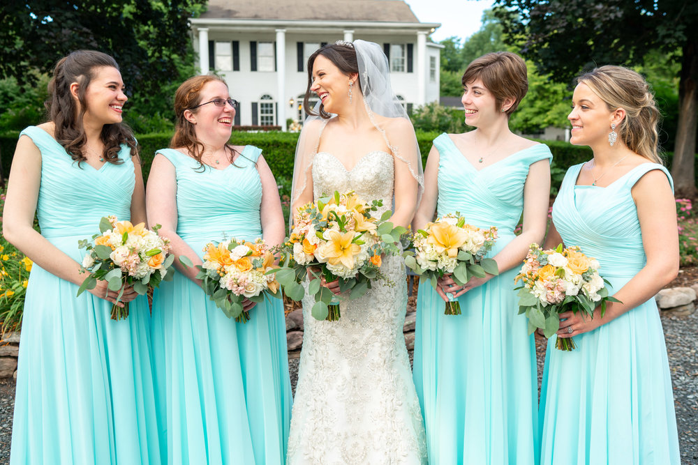 Bride and wedding party in front of Harvest House mansion