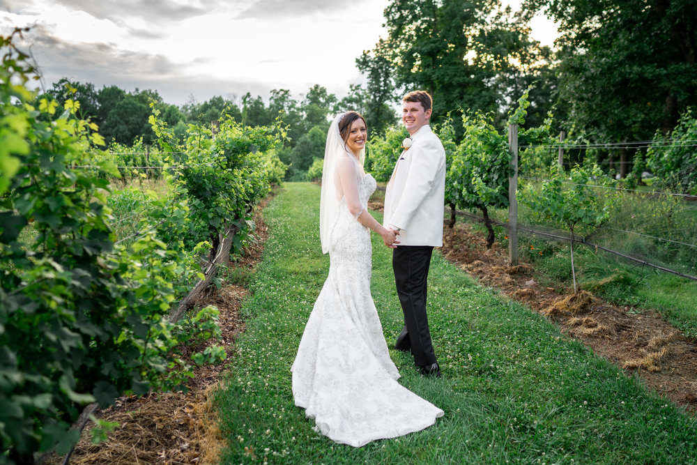 Bride and groom smiling in the vineyard at sunset Lost Creek Winery