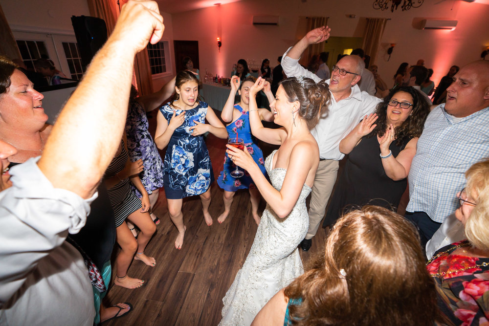 Bride dancing in the center of a group of guests at Harvest House
