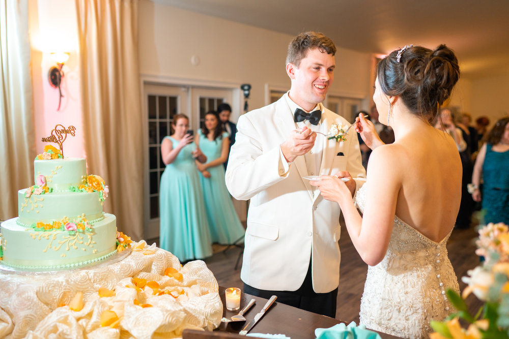 Bride and groom feeding each other wedding cake with forks