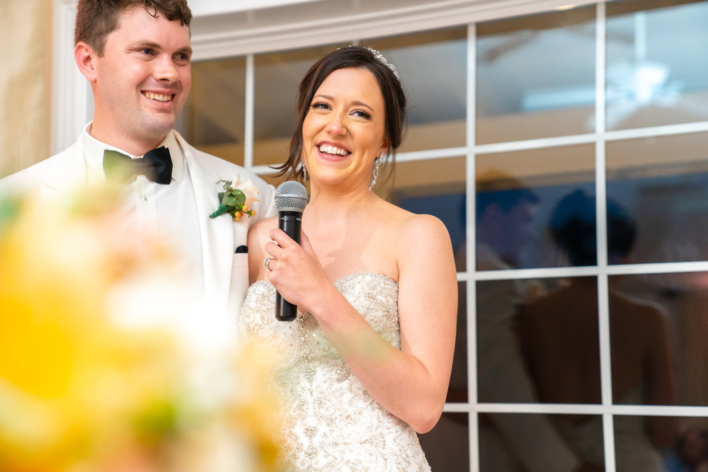 Bride and groom smiling as bride gives thank you toast