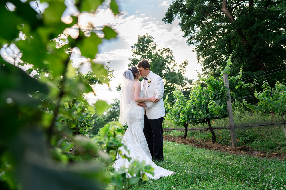 Bride and groom kissing in a dramatic vineyard with sunset at Harvest House