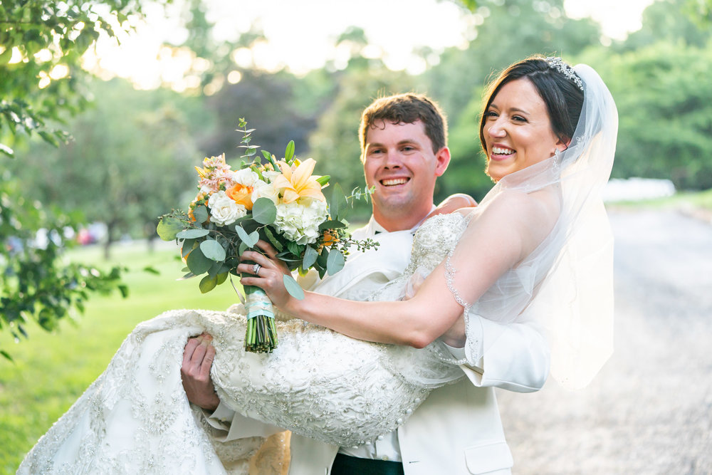 Groom carrying his bride down the gravel path at Lost Creek wedding