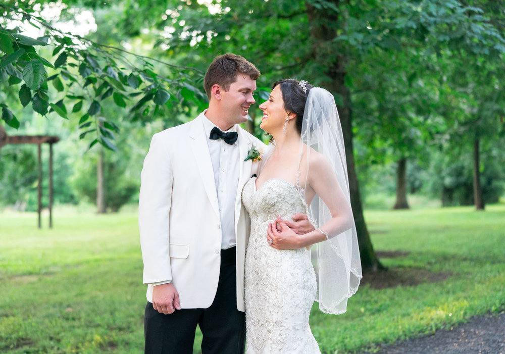 Bride and groom facing each other and smiling