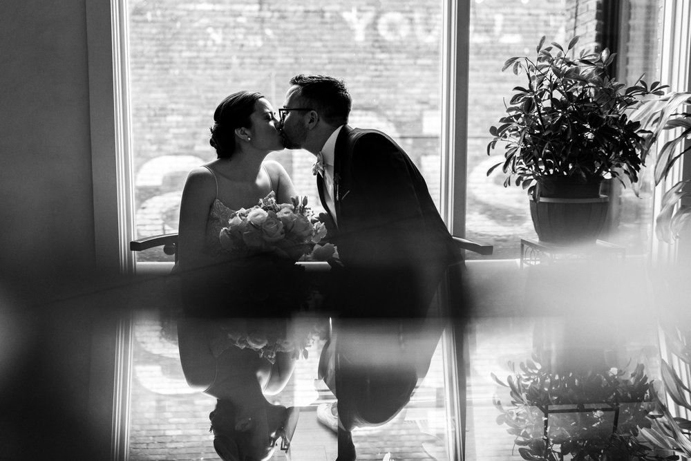 Black and white photo of bride and groom kissing in a window at Gallery OonH