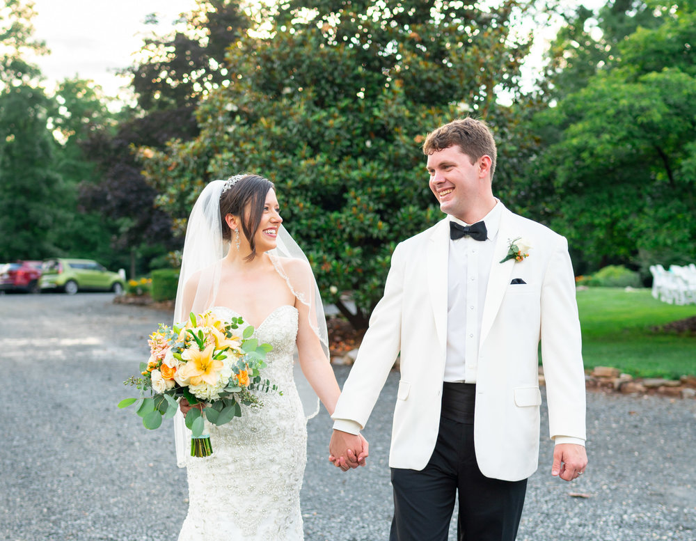 Bride and groom walking down gravel path at Lost Creek Winery