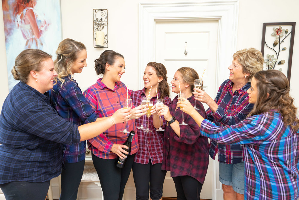 Bride and bridesmaids toasting upstairs at Rust Manor House before wedding ceremony