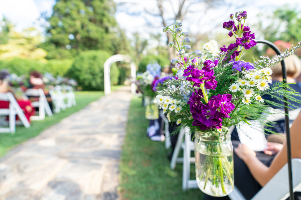 Shepherds hook with purple flowers leading down wedding aisle