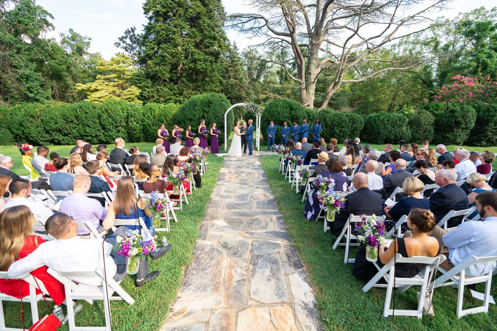 Wide shot of wedding ceremony and guests at outdoor wedding at Rust Manor House with Jeff Maszal