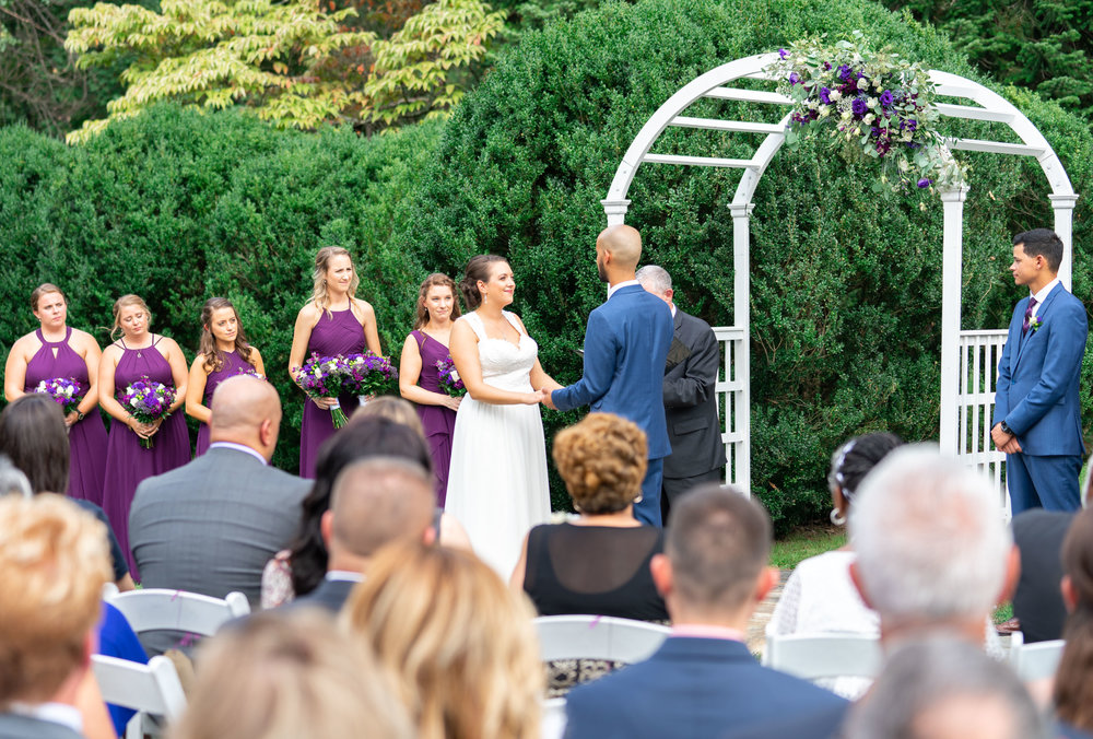 Bride and groom saying their vows under a white arch at Rust Manor House