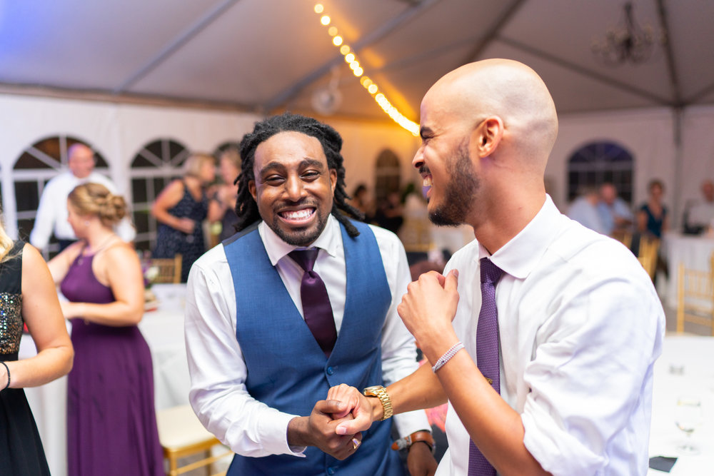Groom and his best man celebrating and dancing with blue uprights