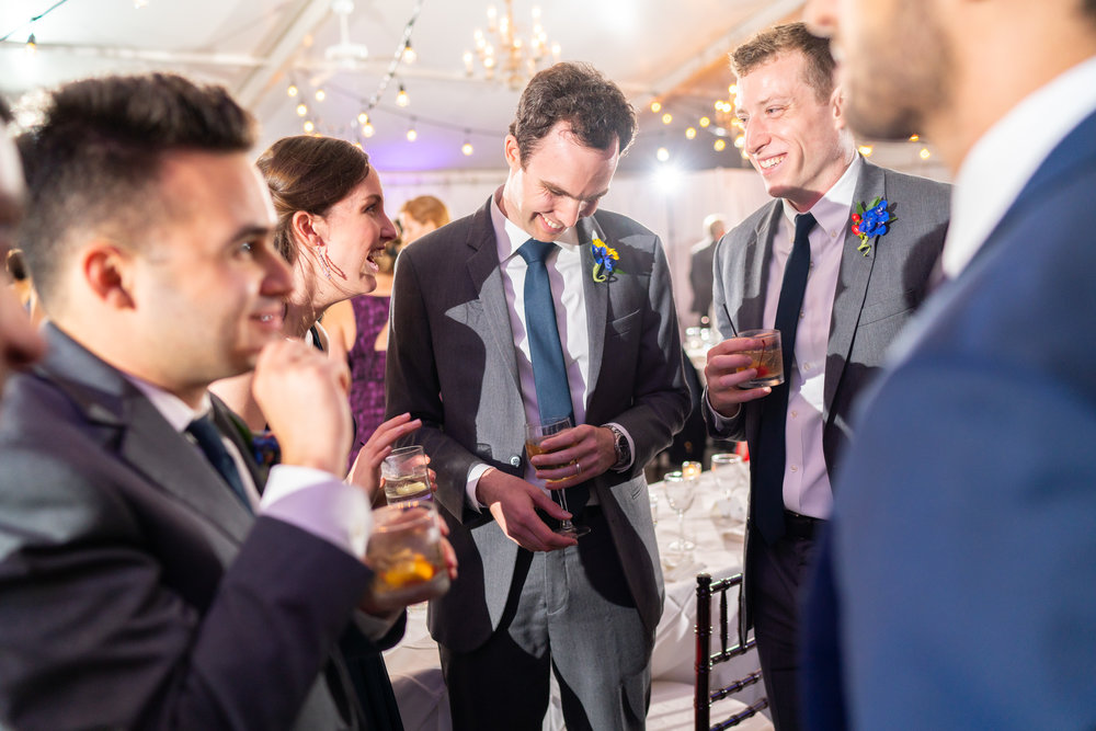 Groom and sister and groomsmen laughing at Elkridge Furnace Inn wedding reception