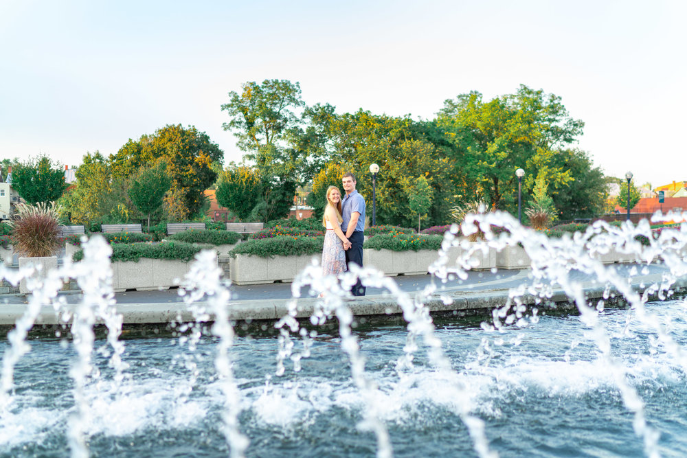 Bride and groom engaged couple standing at the fountains along downtown riverwalk in Frederick Maryland