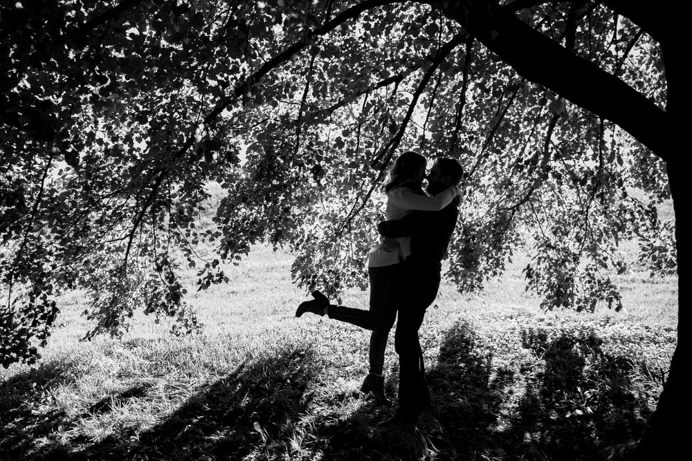 Black and white silhouette of bride and groom under tree at Ft McHenry in Baltimore