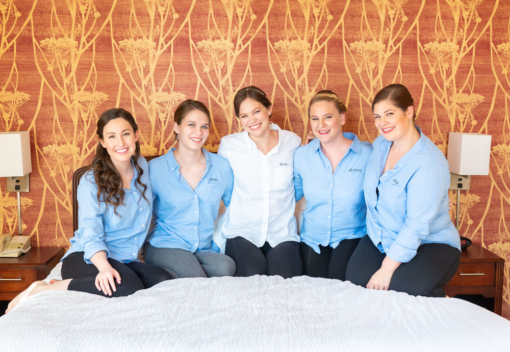 Bride and bridesmaids on bed getting ready photos in Baltimore hotel