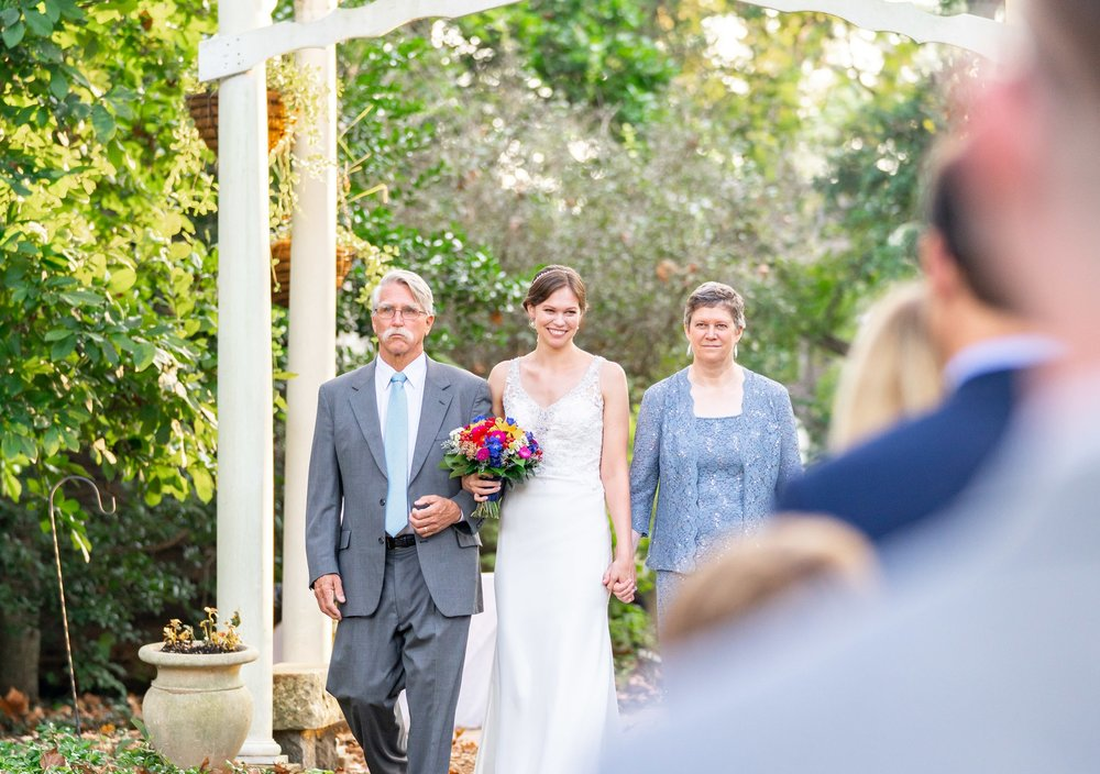 Parents walking the bride down the aisle at outdoor ceremony at Elkridge Furnace Inn
