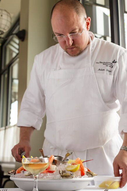 James Beard award winning chef Adam Siegel plating Le Grand Plateau Seafood Tower at Cafe Grace