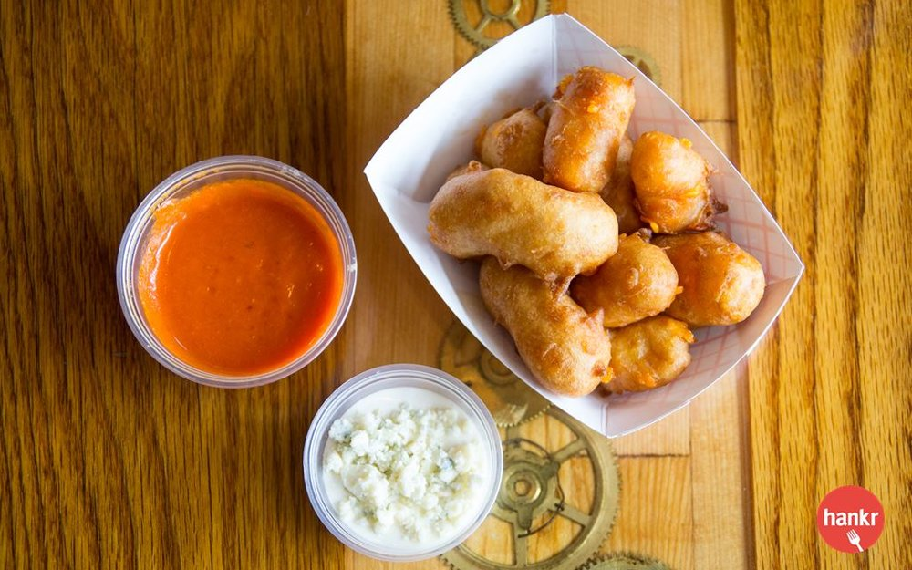 Fresh-battered cheese curds, sourced from Silver Lewis Cheese Factory in Monticello, WI. Served with spicy buffalo sauce and smoked blue cheese.