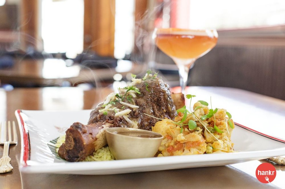 Bheda Lamb Shank. Strauss lamb shank braised with garlic, ginger, onion, cinnamon, cloves, cardamom, cumin, & coriander. Served with rice & seasonal vegetable.