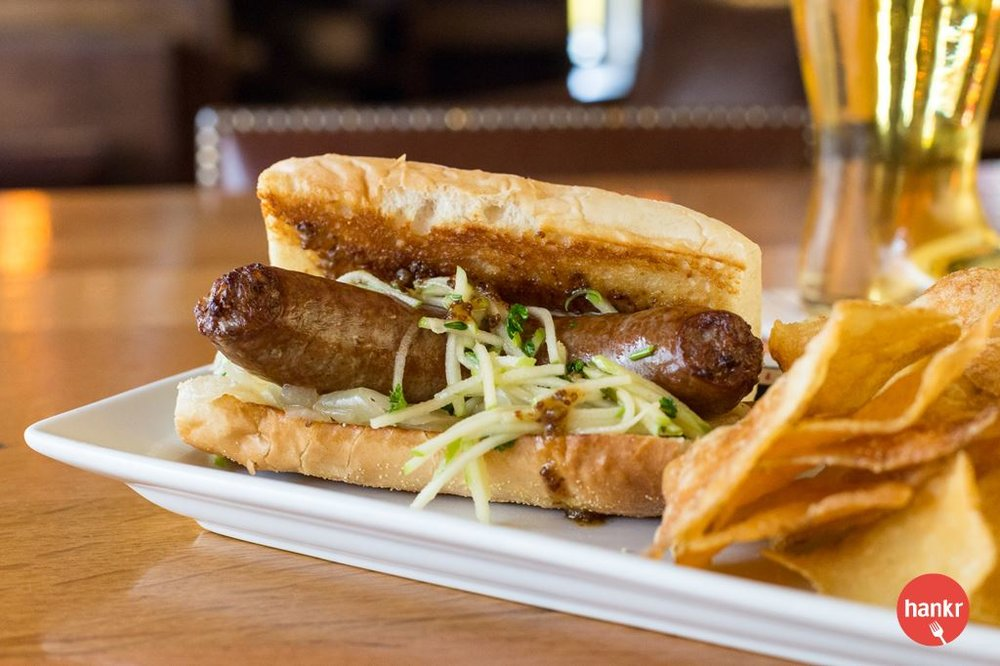 German Style Bratwurst. Usinger's Brat topped with beer onions, green apple slaw, and whole grain honey mustard on a toasted bun.