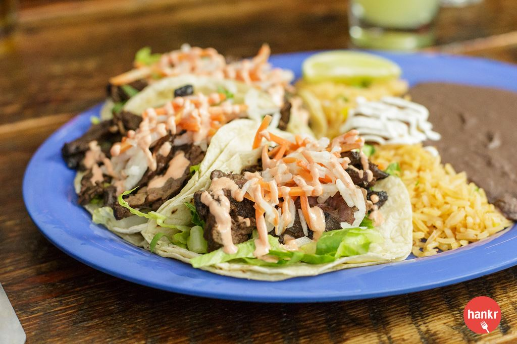 Spicy-sweet marinated beef, lettuce, jicama, carrot, lime, Sriracha crema. $4.45 each. Order 3 tacos, and we'll add a free wave of rice & beans.