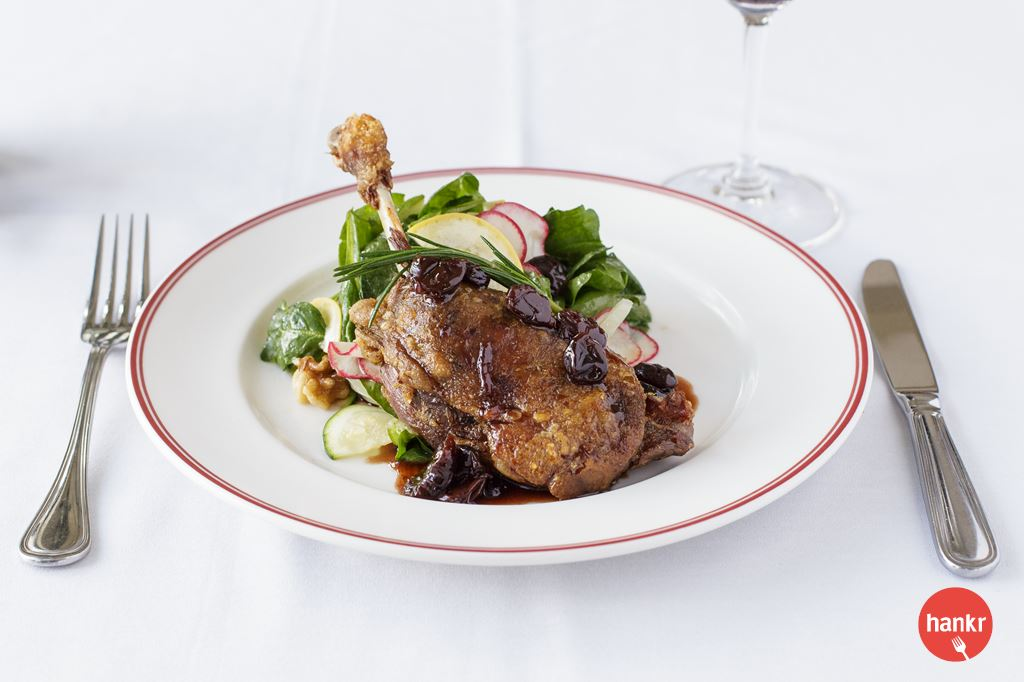 Canard Confit. Slow cooked duck leg with fresh spinach, walnuts and cherry gastrique.
