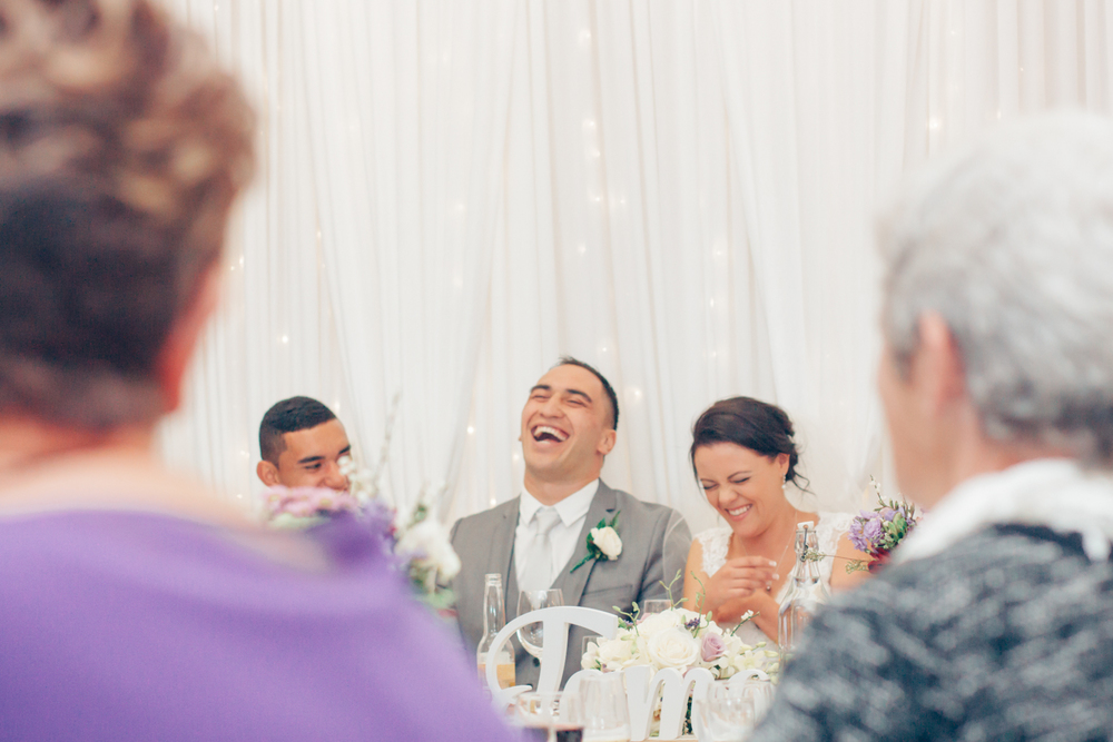 Bride and Groom laugh at wedding reception speeches