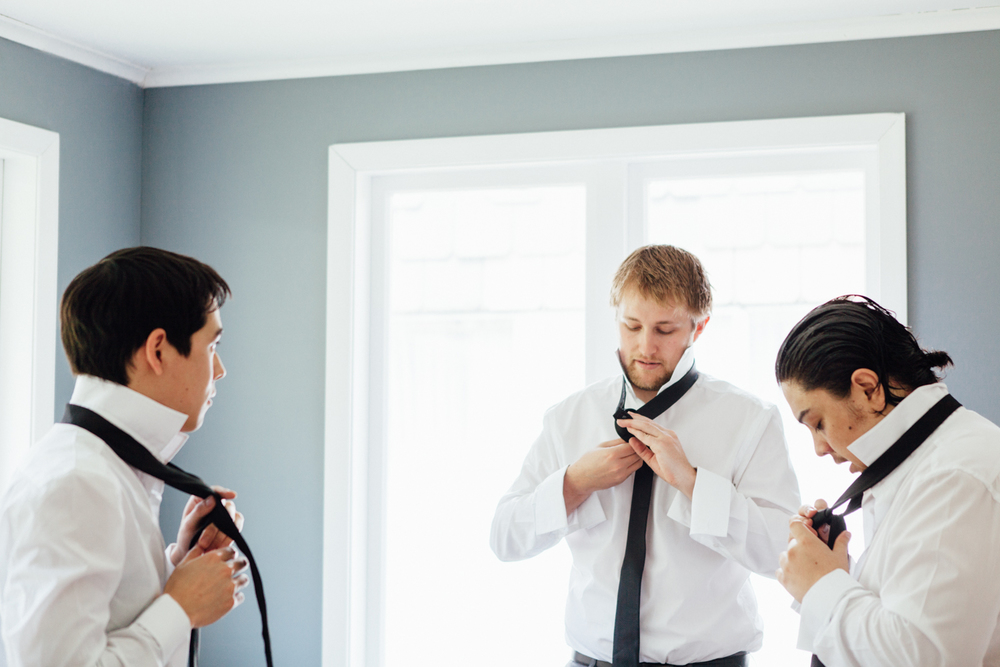Groomsmen tying their wedding ties
