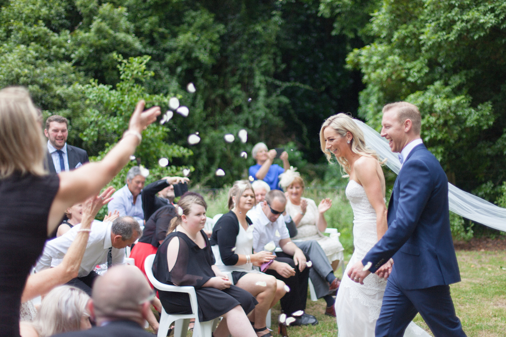 Guests throwing petals in the air as Bride and Groom walk down ceremony aisle