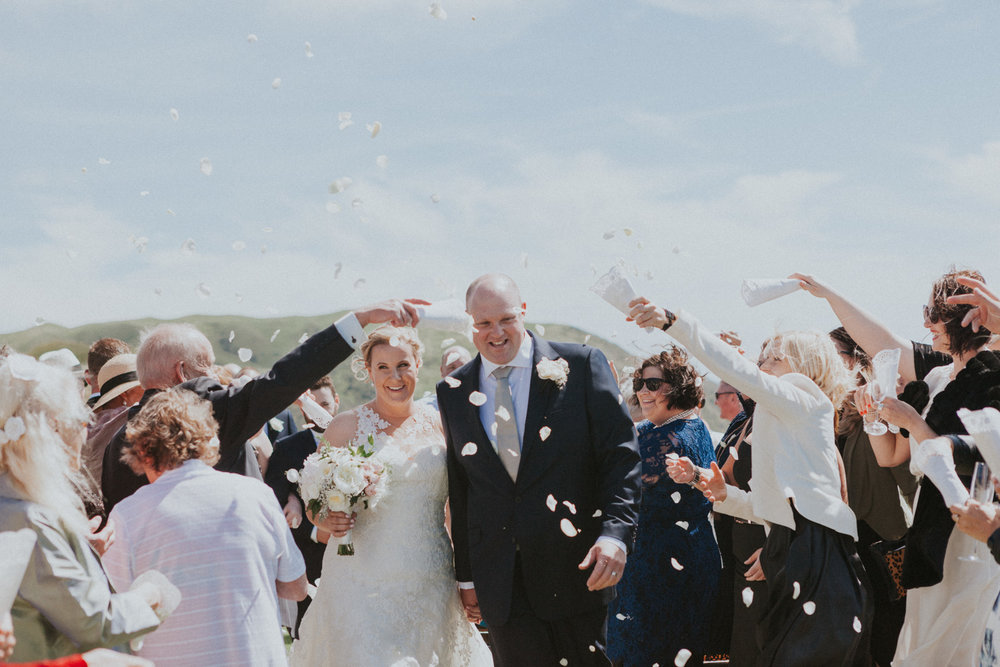 Bride and Groom walk down wedding aisle as guests throw flower petals