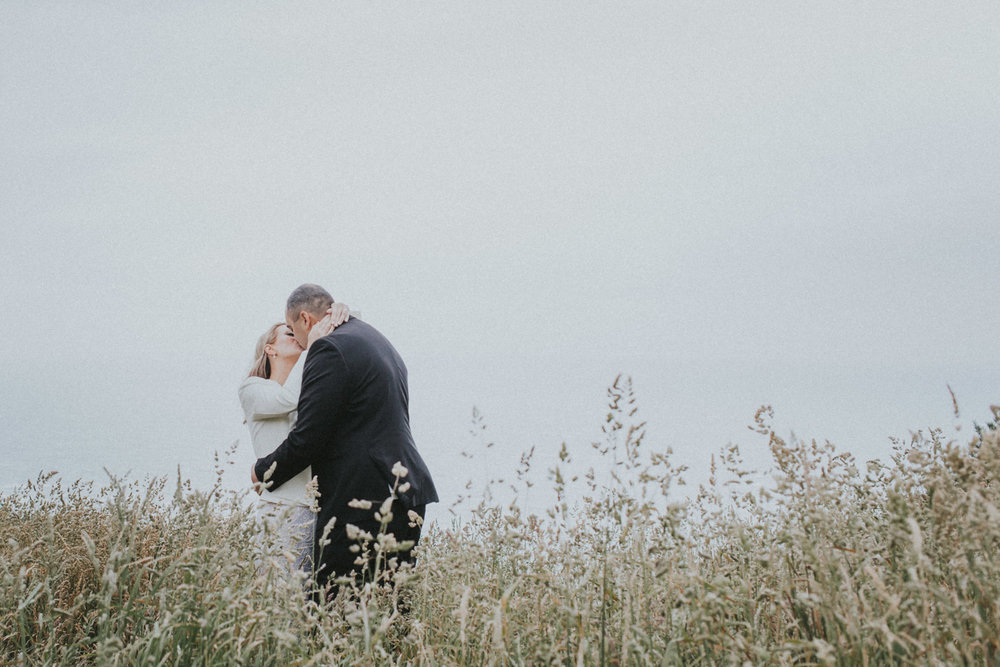 Bride and Groom kiss in the long grass at Boomrock, Wellington wedding venue