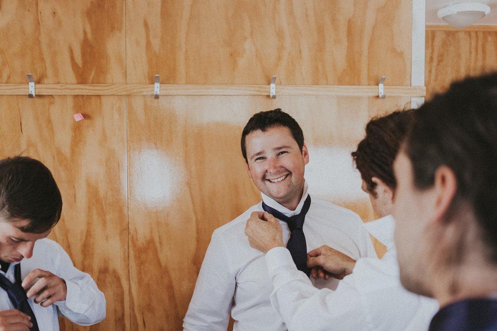 Groomsmen fixing Grooms tie
