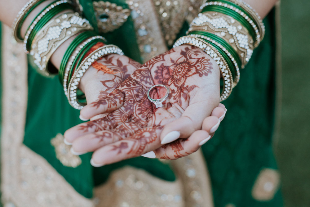 Engagement ring in hands showing henna details